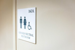 The sign above is the one currently in place to identify existing gender neutral bathrooms on campus. However, the new signage will not include these binary icons. Photo By: Spencer Davis