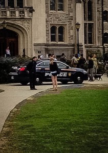 Students and security gathered outside the library on Saturday to watch as a police officer questioned Poughkeepsie residents who had spurred a noise complaint. Photo By: Ruth Bolster