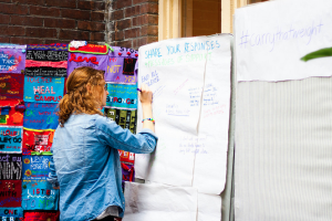 Erin Boss '16 writes a message onto one of four mattresses on display in the Retreat as a part of Vassar's Carry That Weight Day of Action on Wednesday, Oct. 29. Other mattresses featured artwork and statistics about gender violence.