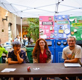 Volunteer staffers sit near the Retreat waste bins that they have gathered together. They hope to increase composting on campus by educating students about composting. Photo By: Emily Lavieri-Scull