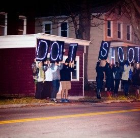 "Vassar students hold up signs reading ""Hands up don't shoot,"" a popular phrase associate with the recent death of Michael Brown, at a night rally on Nov. 25. Photo By: Sam Pianello/"