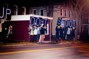"""Vassar students hold up signs reading """"Hands up don't shoot,"""" a popular phrase associate with the recent death of Michael Brown, at a night rally on Nov. 25. Photo By: Sam Pianello/"""