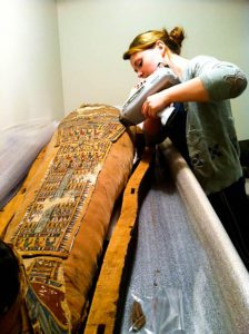 Pictured above, a student restores the sarcophagus of the mummy that lives in the basement of the Loeb. While the Loeb displays ever-changing exhibits, down below these artifacts hang around for years. Photo By: Julie MacDonald
