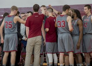 Men's basketball huddles together for guidance from Coach Dunne as they face League competition. The squad will eventually start their season home against SUNY New Paltz on Nov. 15. Photo courtesy of Carlisle Stockton