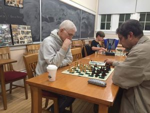 """Chess players young and old gather at the Vassar-Chadwick Chess Club for a battle of wits. Child """"prodigy"""" Trevor Brook mulls over his next move, as pictured above. Photo by Yifan Wang/The Miscellany News"""