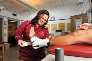 Head Athletic Trainer Suzi Higgins wraps an athlete's ankle before competition. Higgins holds one of the most important roles in making sure athletes are healthy and ready to play. Photo courtesy of Carlisle Stockton