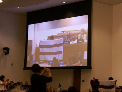 Two Row banner, signed by the paddlers, is presented to the United Nations, August 9, 2013.